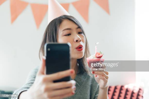 young woman having a virtual birthday party on video call with friends using smart phone - birthday stock pictures, royalty-free photos & images