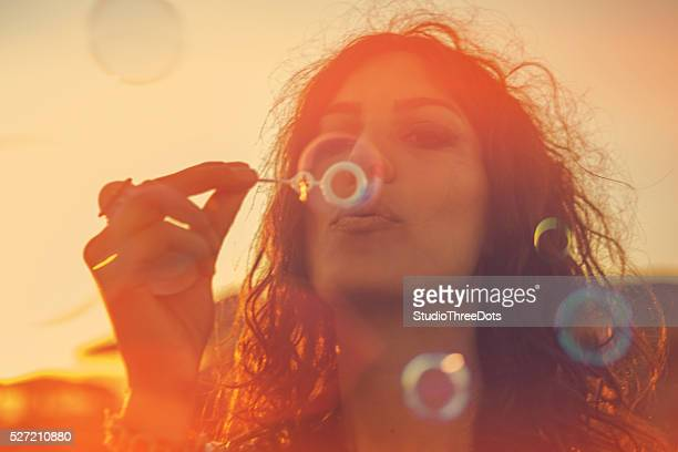 Young woman having blowing bubbles