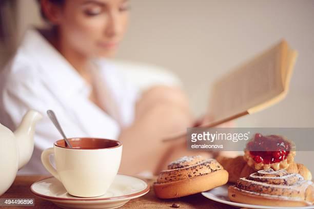 Jovem, tendo o pequeno-almoço e a ler um livro de endereços