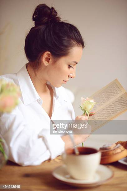 young woman having breakfast and reading a book