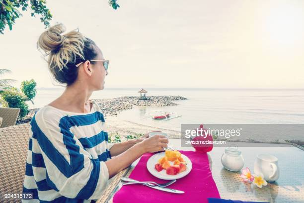 Young woman having breakfast by the sea hotel concept vacations