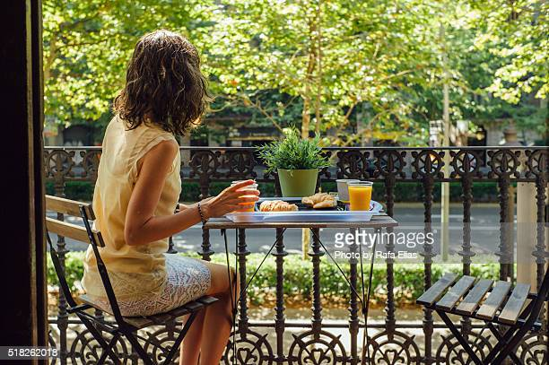 Young woman having breakfast in balcony