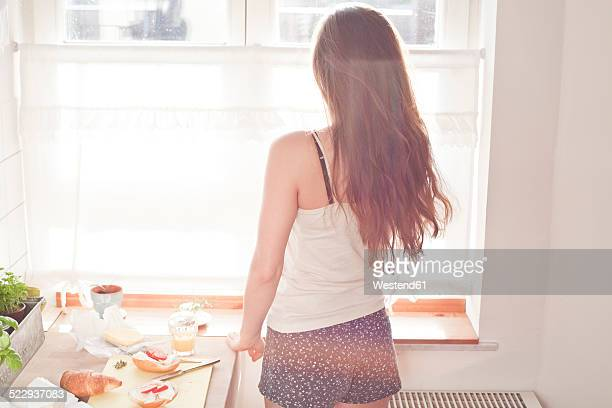 Young woman having breakfast in her kitchen, back view
