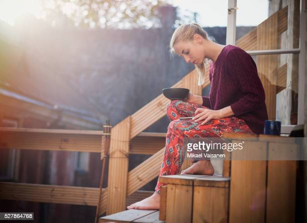 Young woman having breakfast outside on porch with smartphone
