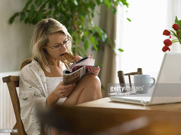 young woman having breakfast while reading magazine - magazine stock pictures, royalty-free photos & images
