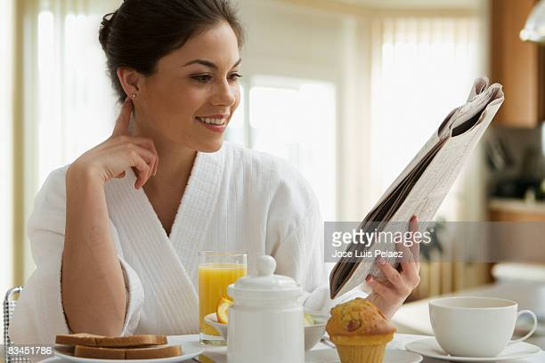 Young woman having breakfast while reading newspap