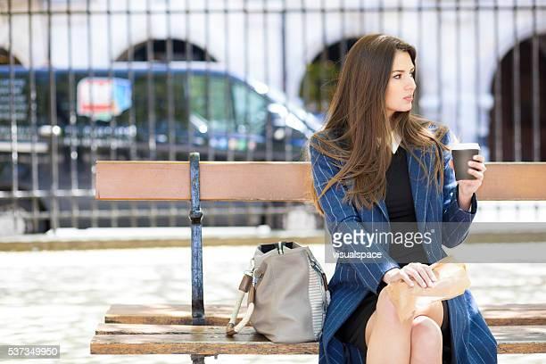 Jeune femme ayant le café et des en-cas, assis sur un banc de musculation