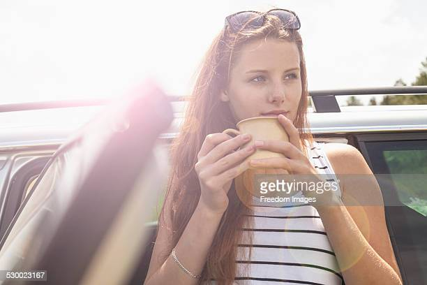Young woman having coffee break on road trip