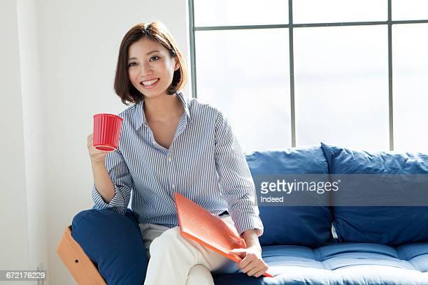 Young woman having coffee on sofa