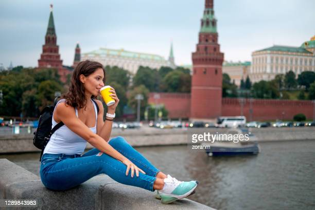 young woman having coffee to go from disposable coffee cup and looking into distance, sitting with feet up on stone fence of bolshoy kamenny bridge over the moskva river, kremlin wall with the grand kremlin palace in blurred background - state kremlin palace stock pictures, royalty-free photos & images