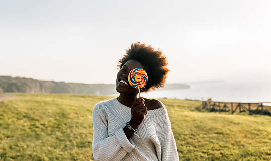 Young woman having covering eye with a lollipop, laughing - gettyimageskorea