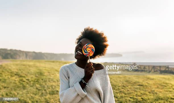 Young woman having covering eye with a lollipop, laughing