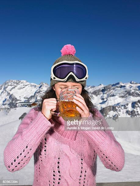 young woman having drink at mountains - meribel stock photos and pictures