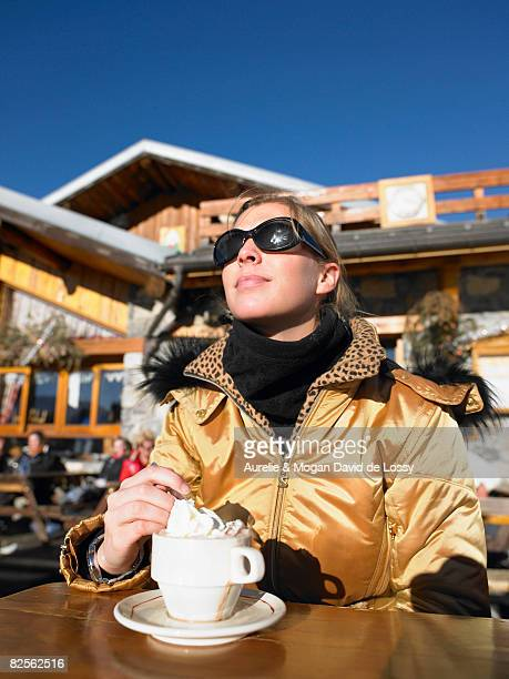 Young woman having drink on terrace