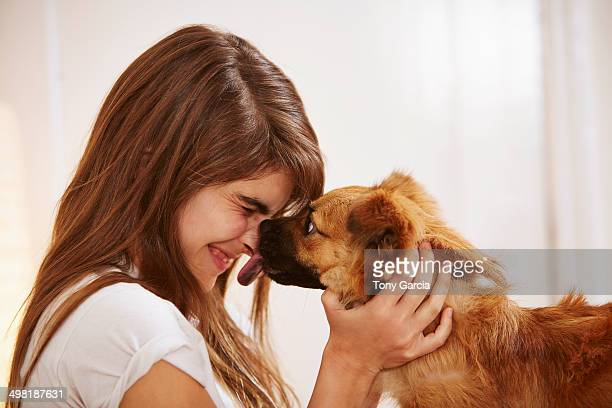 Young woman having face licked by pet dog