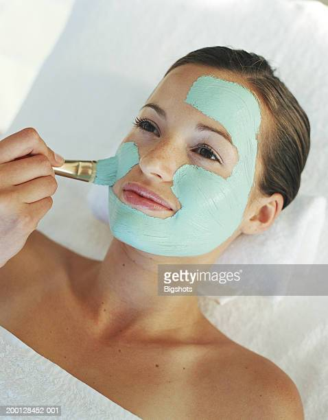 young woman having face mask applied, close-up - bronzage masque photos et images de collection