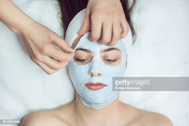 Young woman having face mask applied