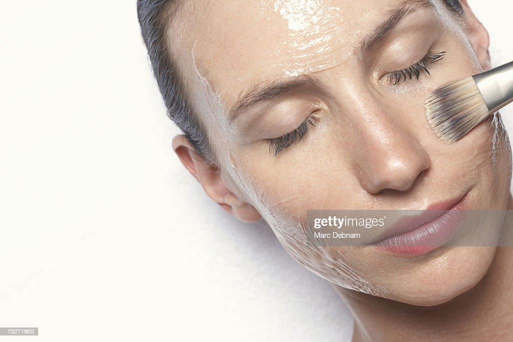 Young woman having facial treatment, close-up : Stock Photo