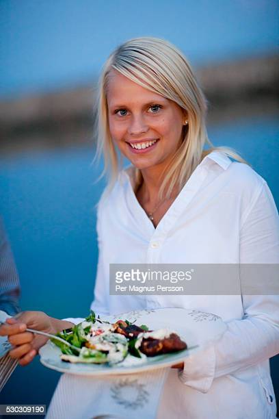 Young woman having food at coast, portrait, smiling