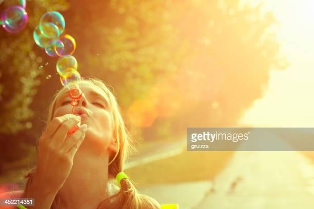 Giovane donna che si diverte e soffiare le bolle d'aria aperta
