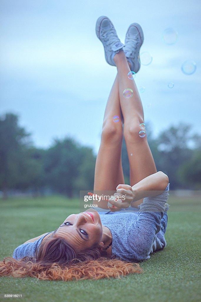 Jovem mulher a divertir-se e mandar bolhas de ar livre : Foto de stock