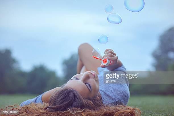 若い女性が楽しく吹く泡屋外