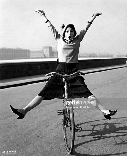 A young woman having fun balancing on a bicycle with legs and arms open wide 1960s
