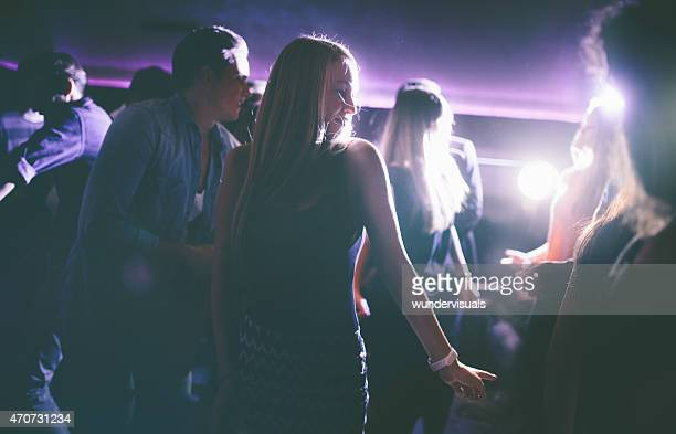 Young woman having fun dancing at party in club