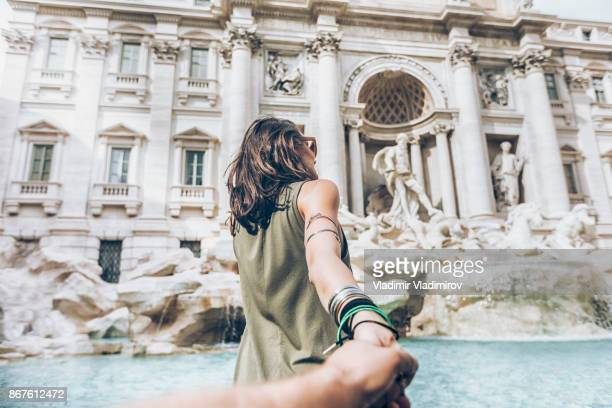 young woman having fun in front of trevi fountain - following stock pictures, royalty-free photos & images
