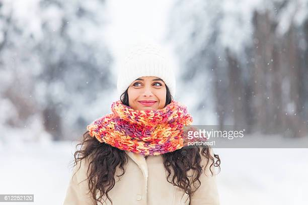 Young woman having fun in the snow forest