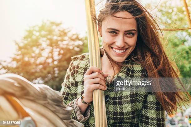 Young woman having fun on a carousel