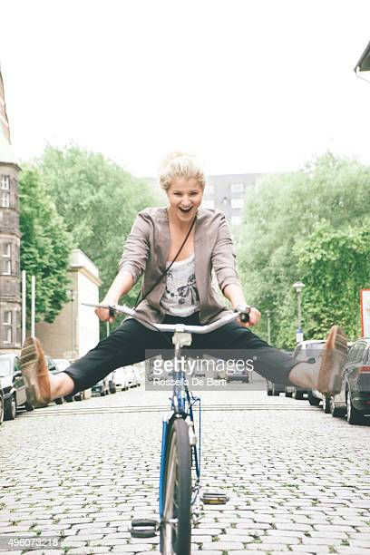 young woman having fun riding her bike in city streets - legs apart stock photos and pictures