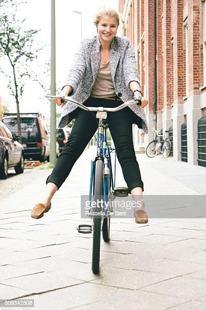 Jeune femme s'amuser équitation son vélo dans les rues de la ville