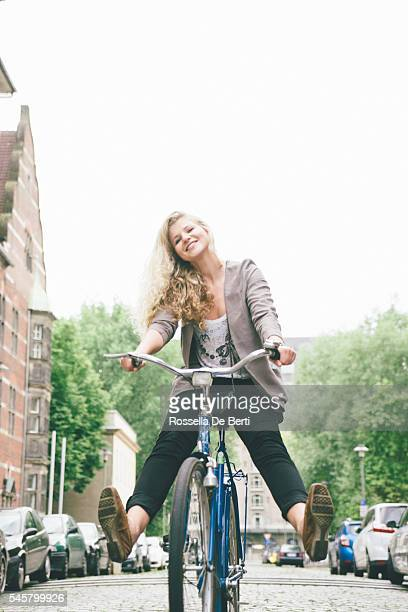 young woman having fun riding her bike in city streets - legs spread woman stock photos and pictures