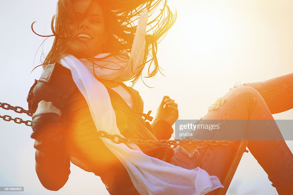 Young woman having fun swinging in sunlight : Stock Photo