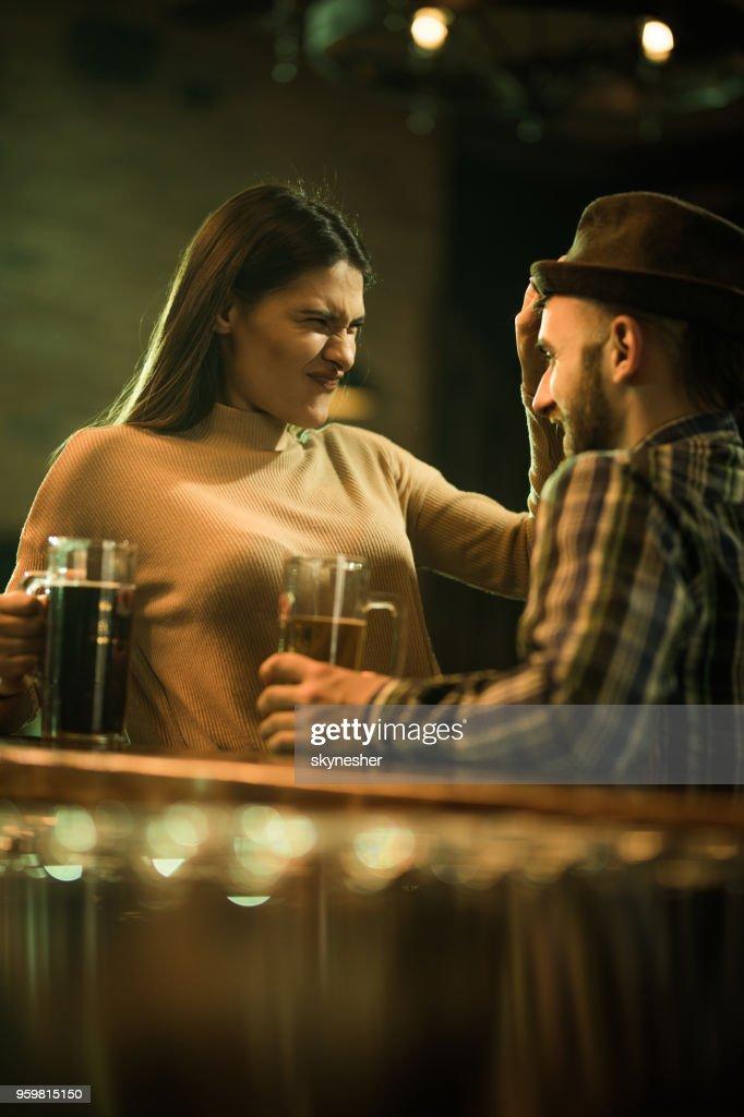 Junge Frau, die Spaß mit ihrem Freund am Tresen. : Stock-Foto