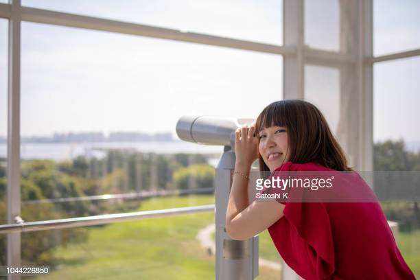 Young woman having fun with telescope in public park