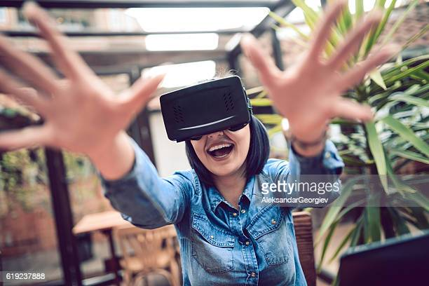 young woman having fun with virtual reality simulator and gesturing - curiosity stock photos and pictures