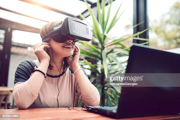 Young Woman Having Fun with Virtual Reality Simulator with Headphones