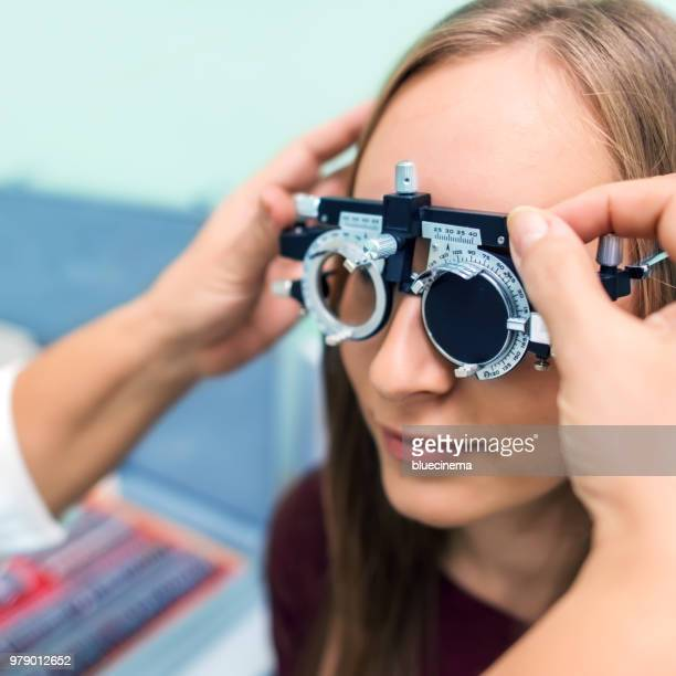 Young woman having her eyes checked at ophthalmologist