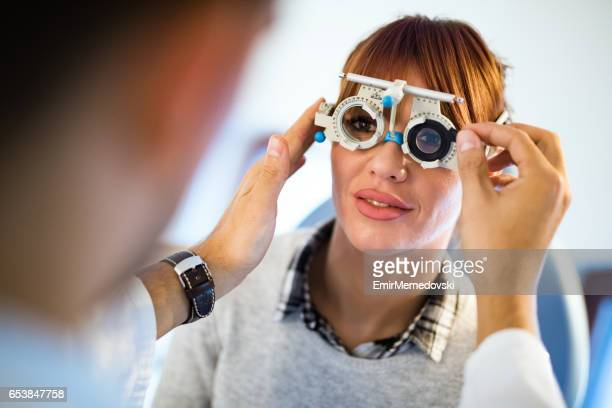 Young woman having her eyes examined by optometrist.