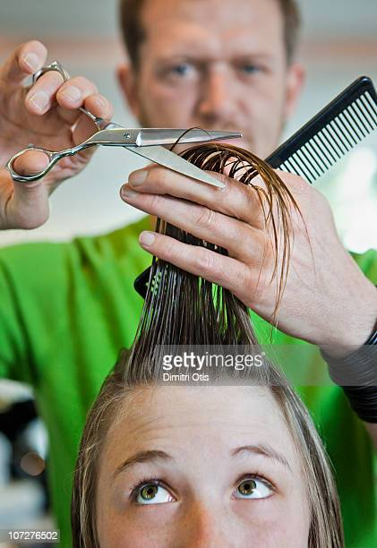 Young woman having her hair cut