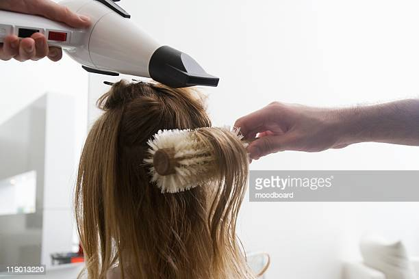 A young woman having her hair dried in the hairdressers
