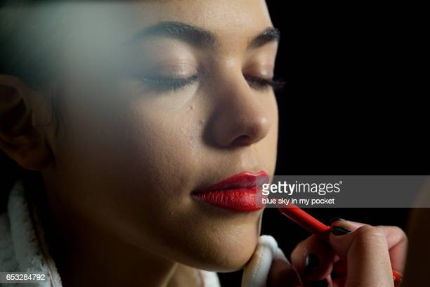 A young woman having her lips painted by a make-up artist.