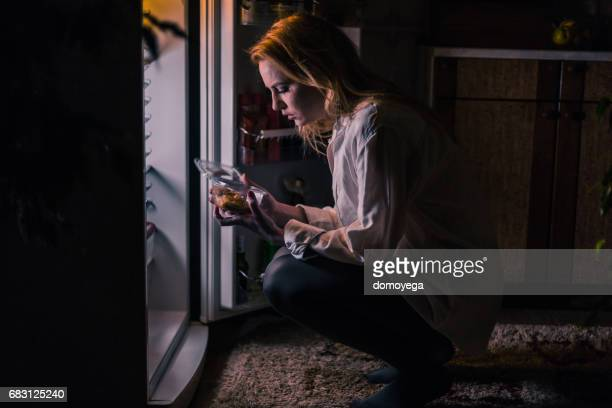 Young woman having late night snack