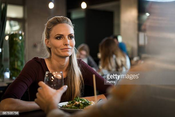 Young woman having lunch with friend in restaurant