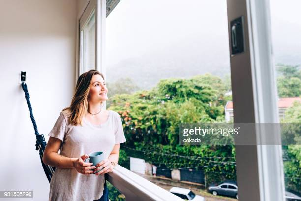 Young woman having morning coffee by the window