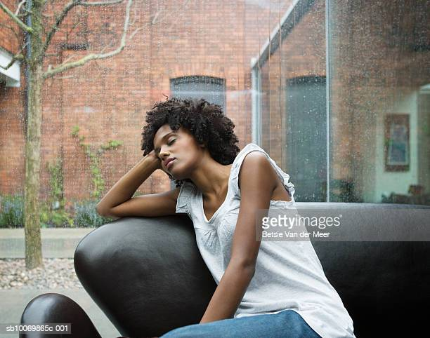 young woman having nap on sofa in living room - sleeping stock pictures, royalty-free photos & images