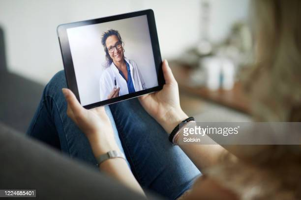 young woman having online meeting with female healthcare person - santé et médecine photos et images de collection