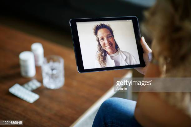 young woman having online meeting with female healthcare person - テレビ会議 ストックフォトと画像